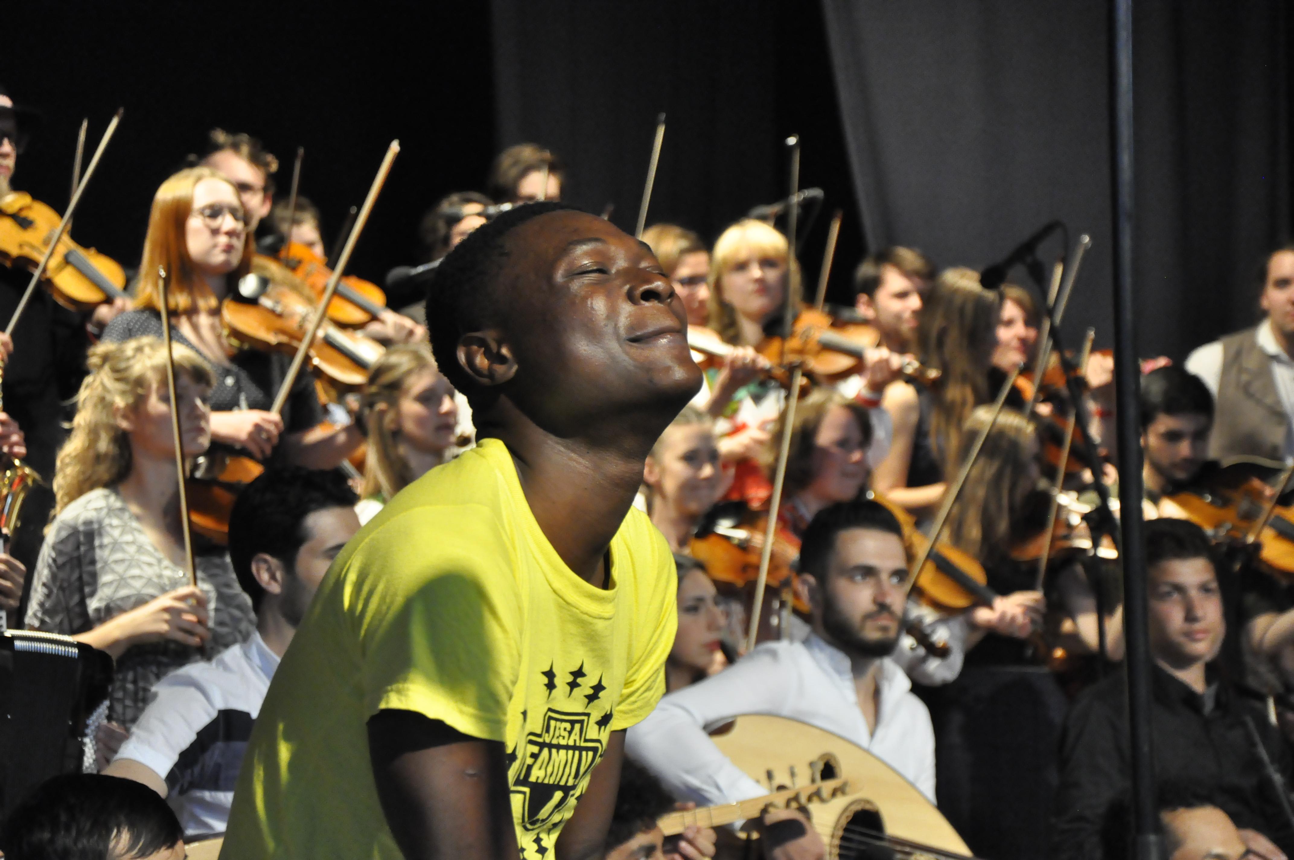 En Glad Ung Slagverkare Framför En Stor Grupp Av Unga Musiker På En Scen