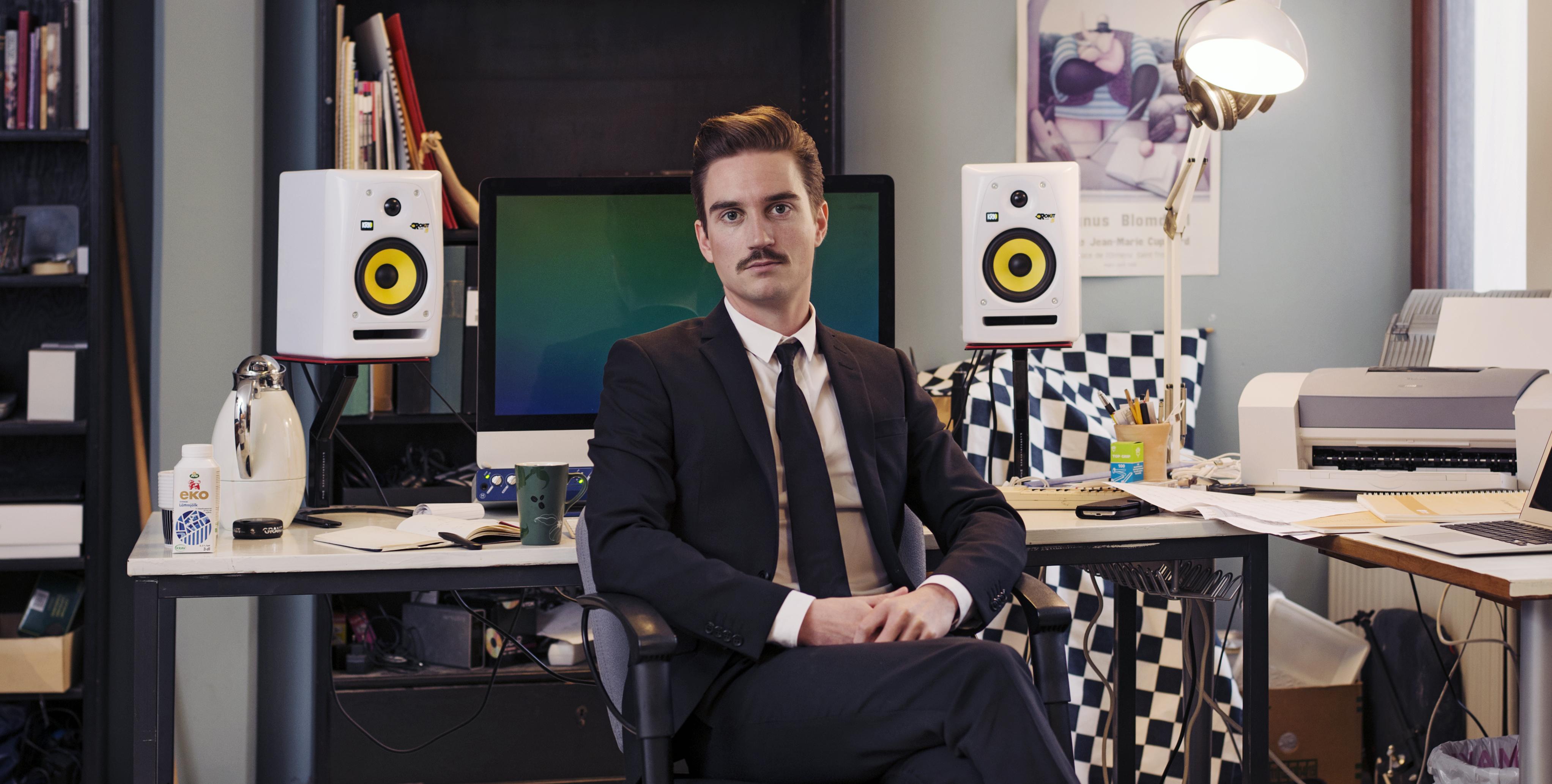 En Man I Kostym Som Sitter Med Ryggen Mot En Datorskärm Och Högtalare