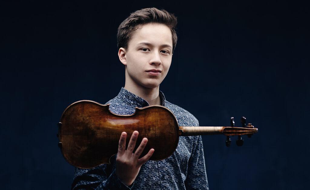 En ung man som håller i sin fiol