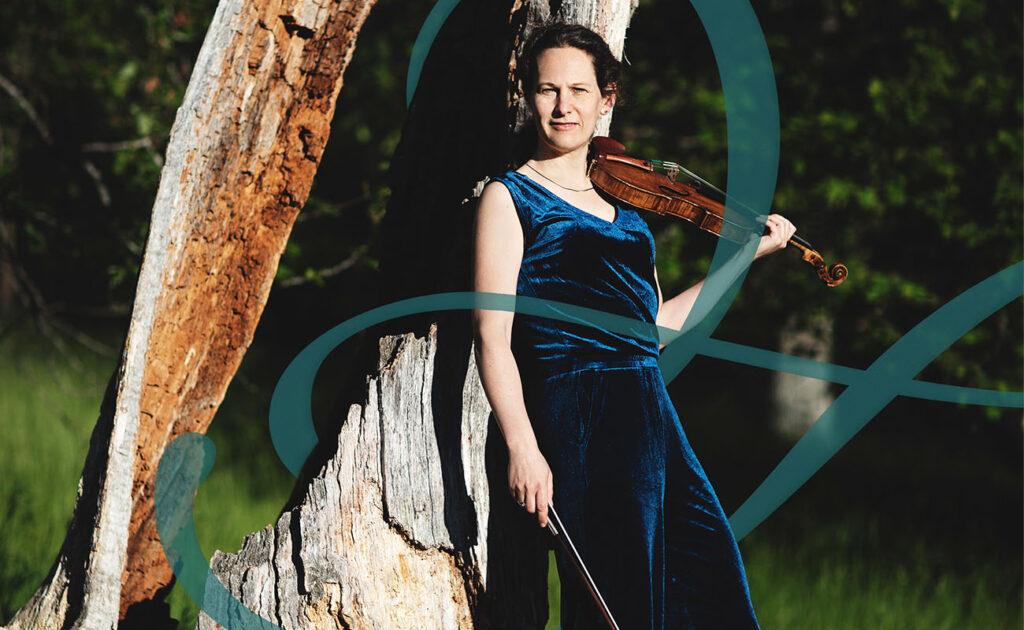En kvinnlig musiker ihållandes en violin stående vid ett dött träd